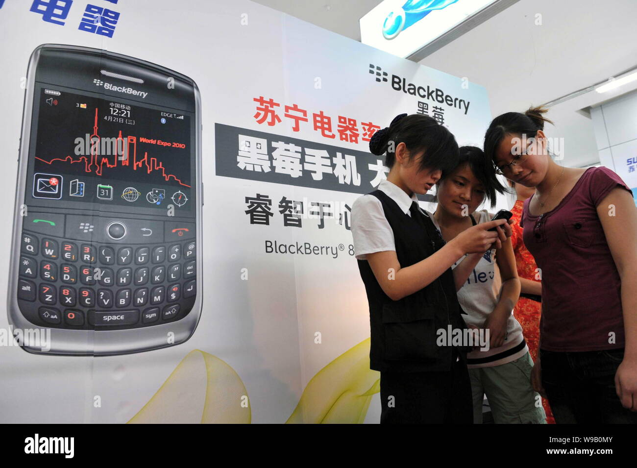A saleswoman introduces customers a BlackBerry 8910 at a
