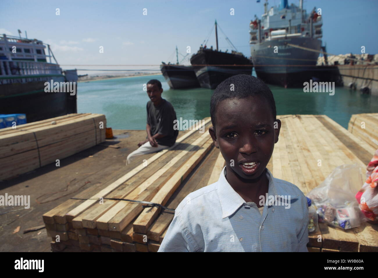 Somali workers pose next to wood products at the harbor in