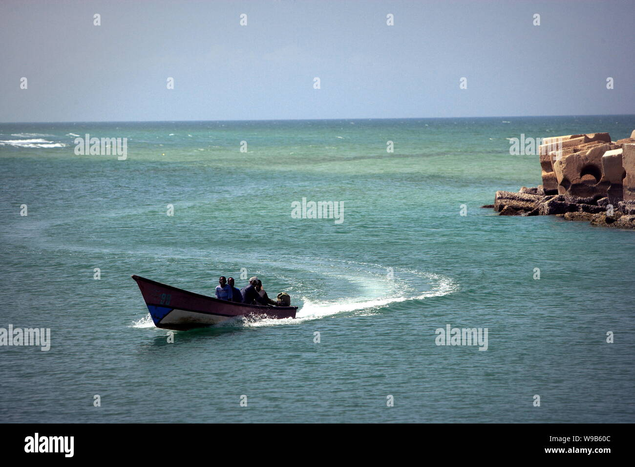 Somali fishermen return in a fishing boat to the harbor in