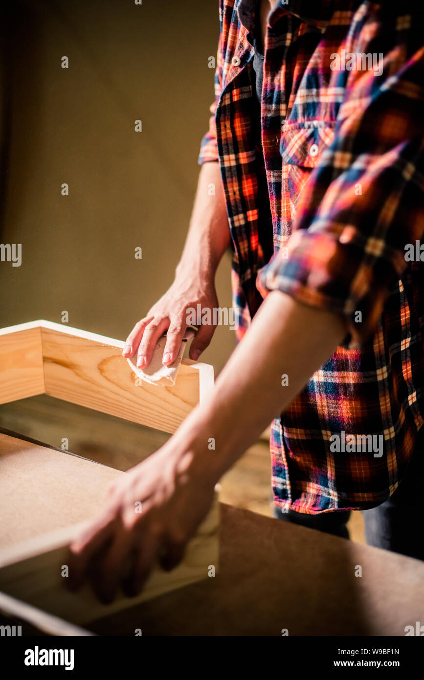 Young handsome joiner working with wood in his carpentry workshop, woodworker business owner Stock Photo
