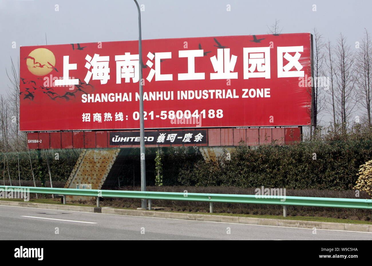 --FILE--A signboard for the Shanghai Nanhui Industrial Zone is seen on the roadside of a highway in Nanhui District in Shanghai, China, 17 March 2005. Stock Photo