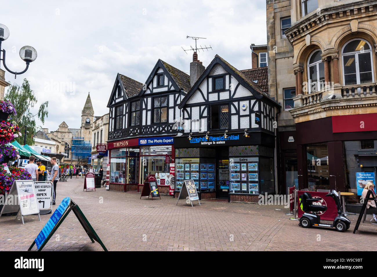 3 shops on Fore street Trowbridge in a Mock Tudor building with market day traders visible in the street Stock Photo