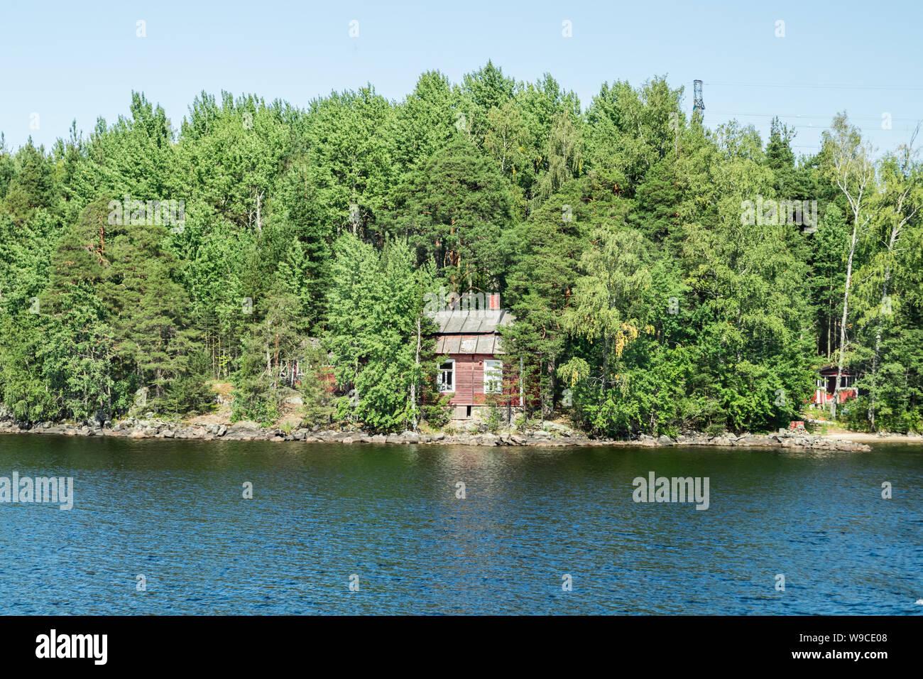 Red small finnish wooden house on island on the lake Saimaa. Lappeenranta, Finland. Stock Photo