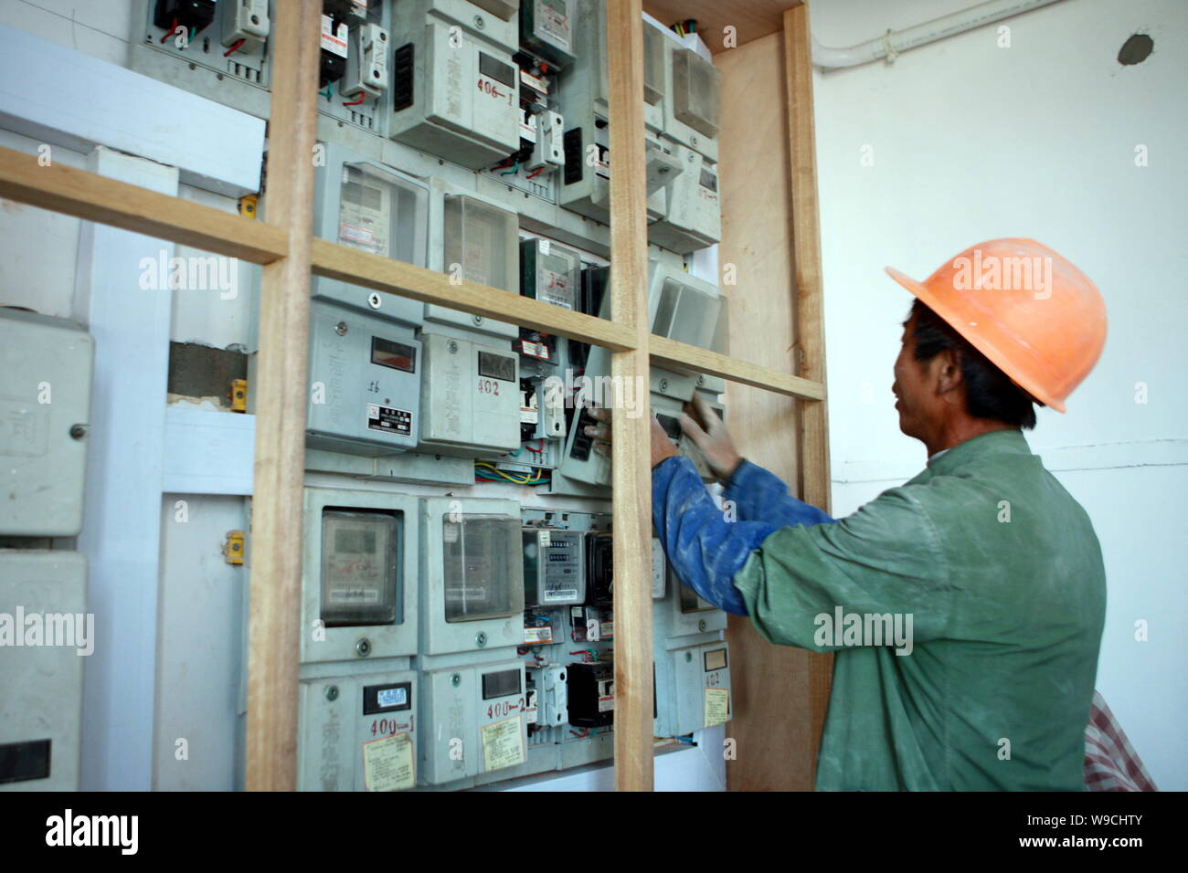 A Chinese worker checks watt-hour meters in Wukang Building