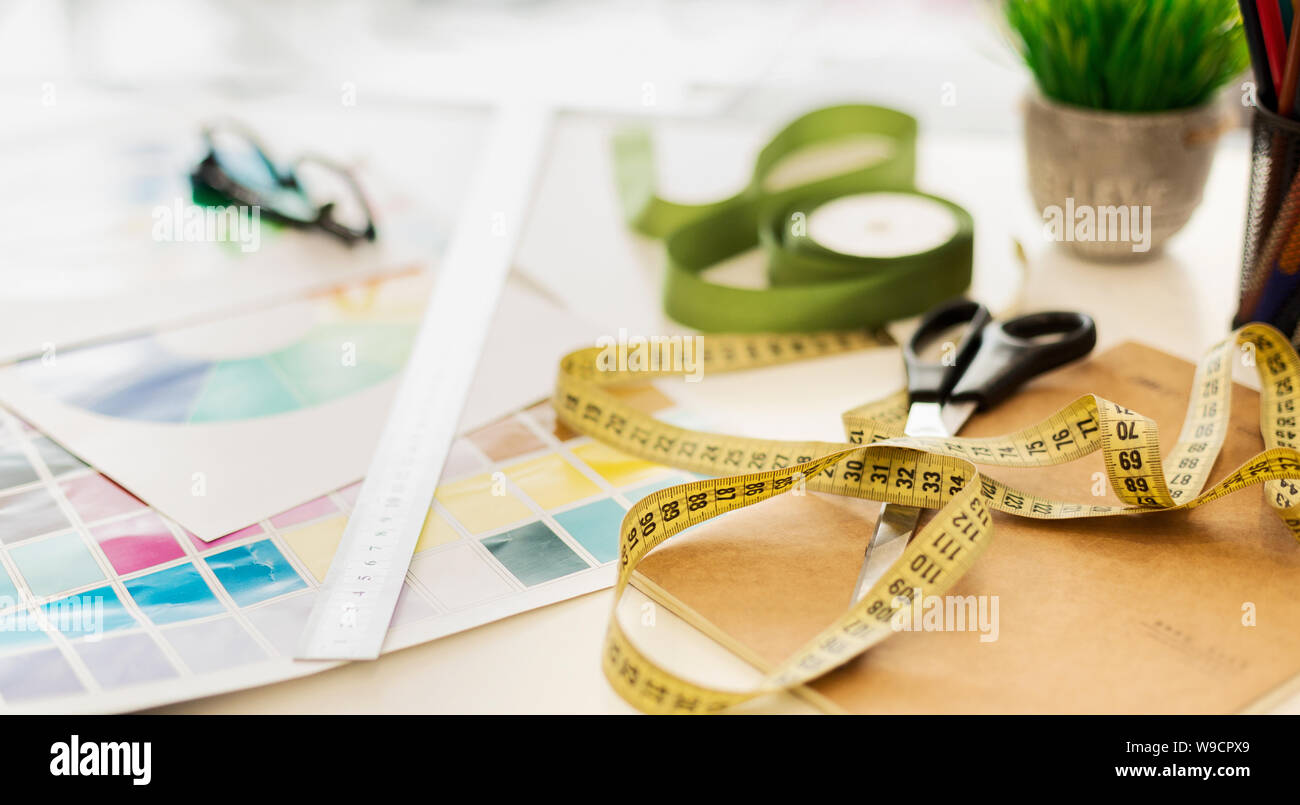 Closeup Of Fashion Designer Workplace With Measuring Tape And Color Samples Stock Photo
