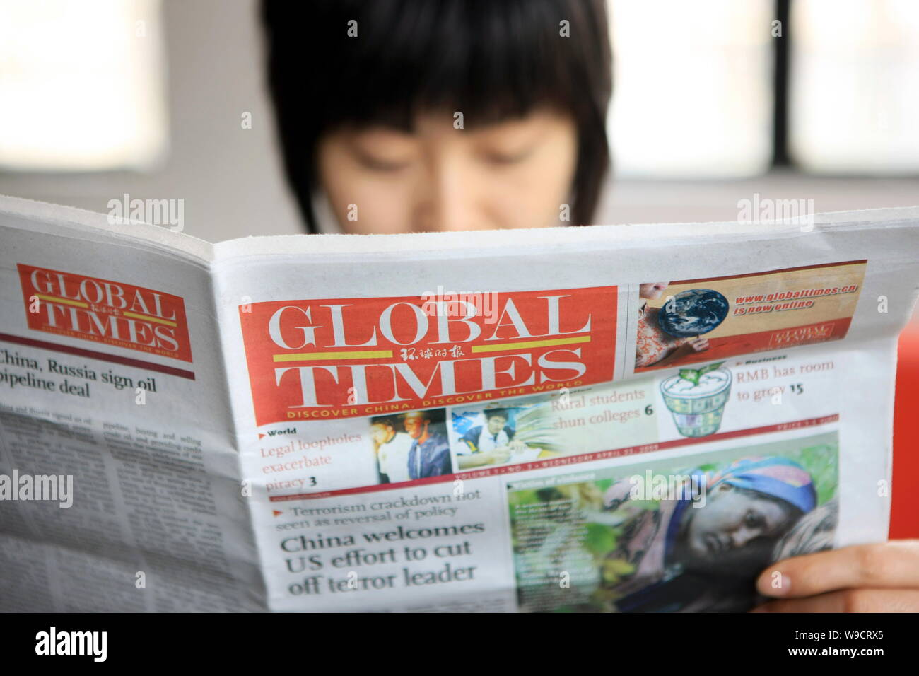 A young Chinese woman reads a Global Times newspaper in the office ...
