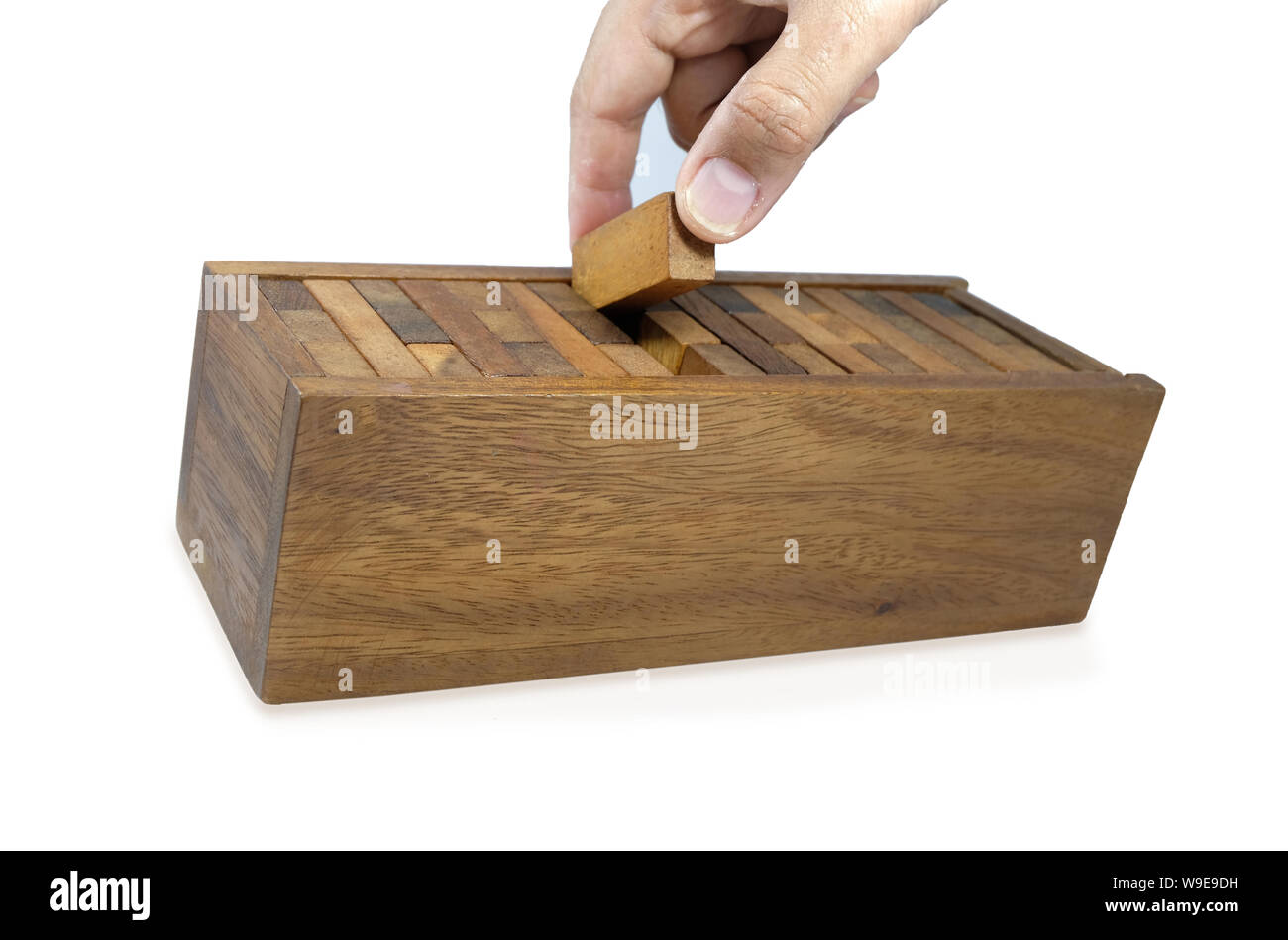 Hand is collecting pieces of wooden bricks in the box after
