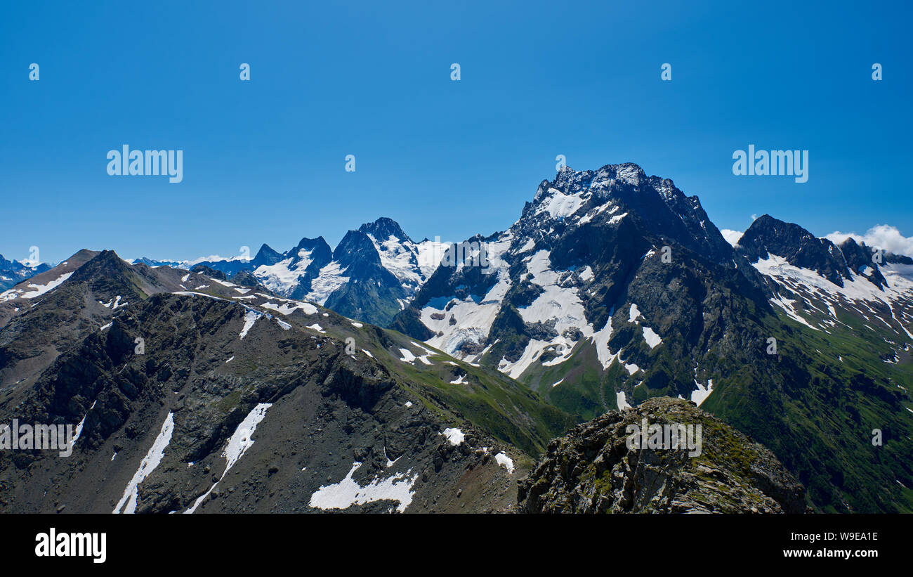 The black mountain peak in the foreground is a rocky ridge. North Caucasus, Russia Stock Photo