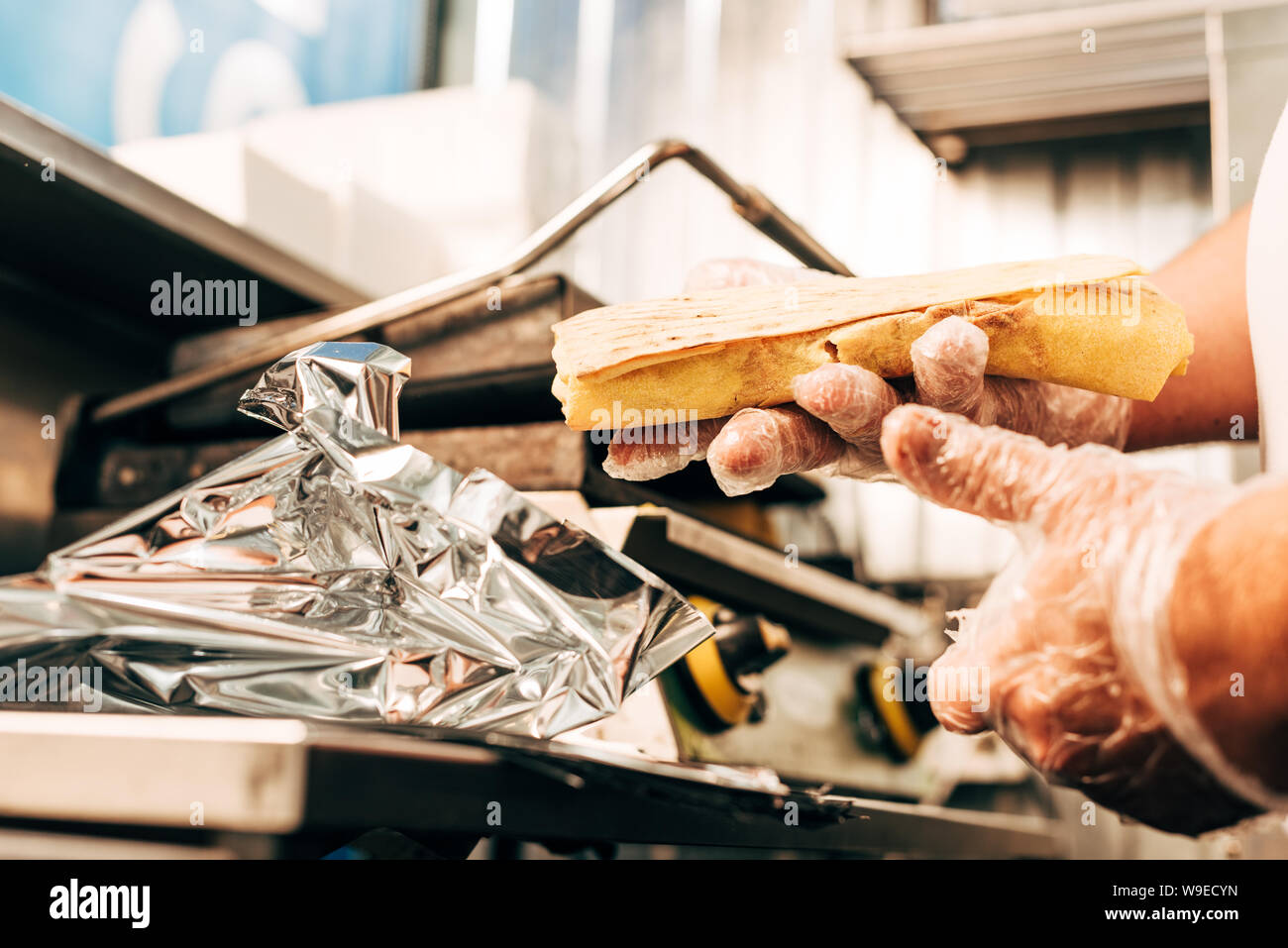 Partial View Of Cook In Gloves Using Aluminium Foil While