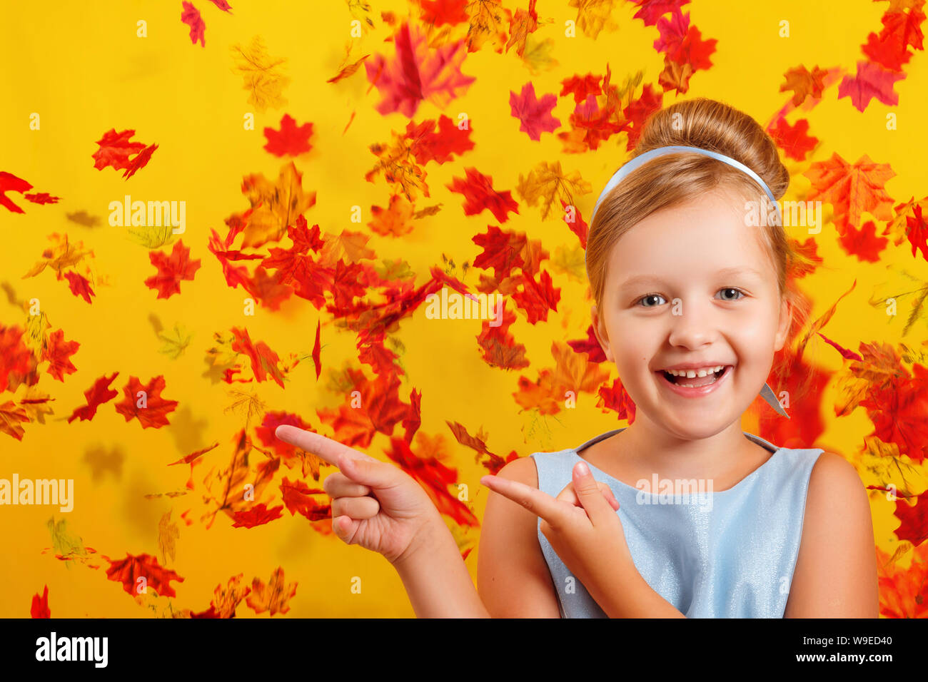 Cheerful little girl in a costume of Princess Cinderella on a background of falling autumn leaves. The child shows the index fingers to the side. Conc - Stock Photo