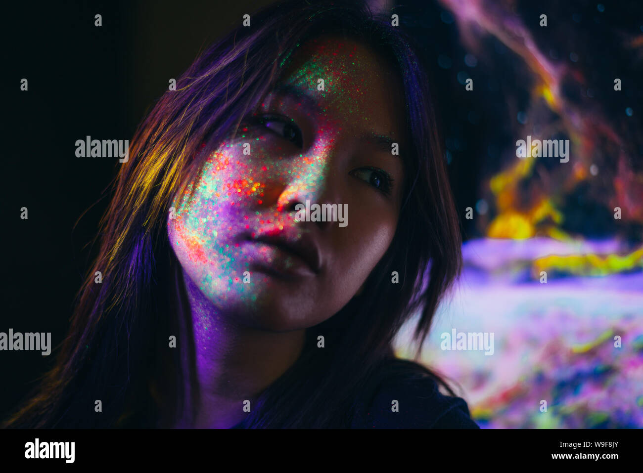 Beautiful young woman dancing and making party with fluorescent painting on her face. Neon facial portraits Stock Photo