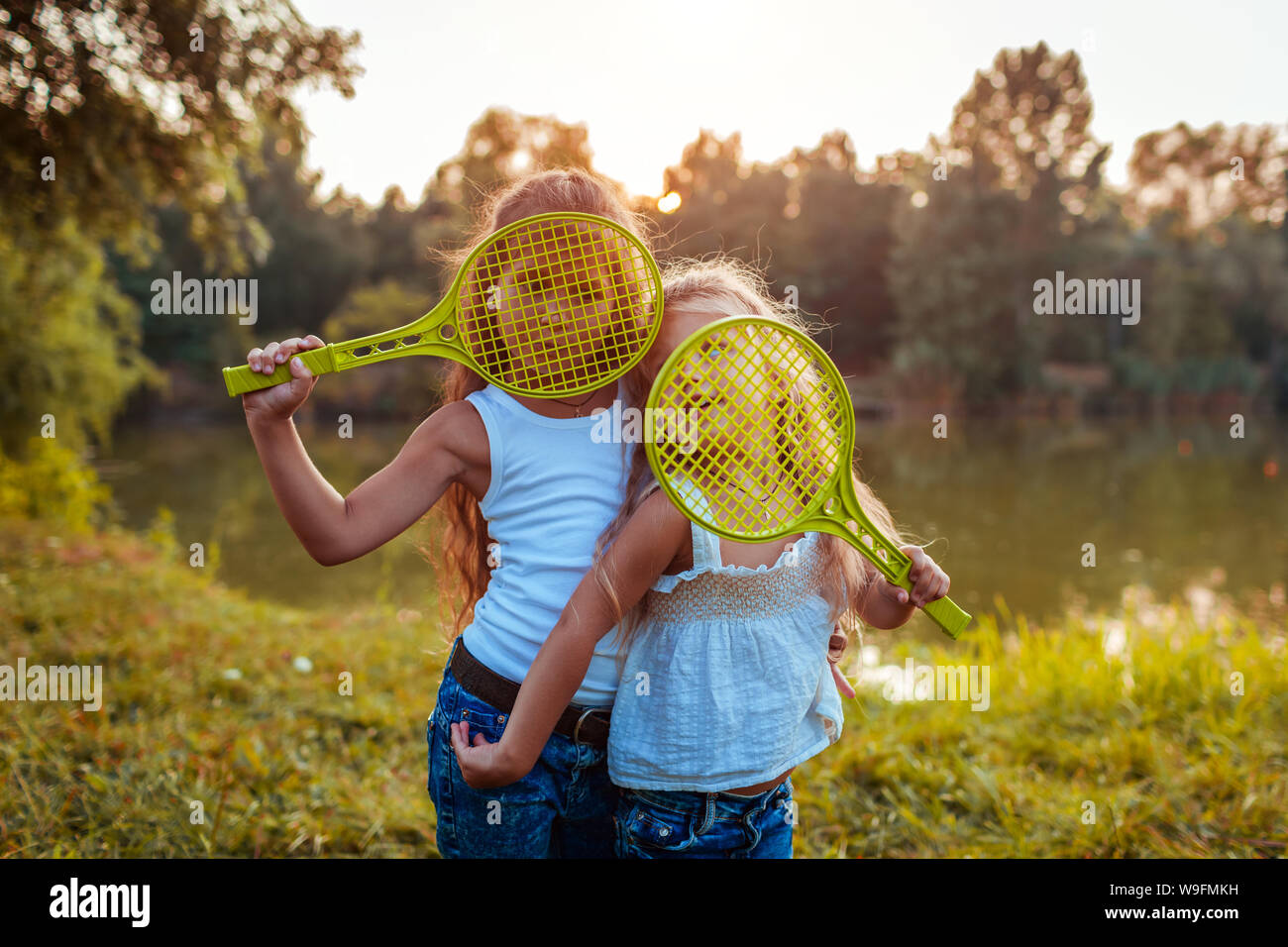 Little girls having fun outdoors after playing badminton. Sisters cover faces with rackets in summer park. Kids. International Childrens Day Stock Photo