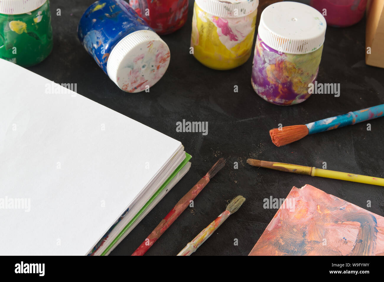 Painting artist desktop in the studio. Some paintbrushes and material ready for an art lesson in a classroom. Empty copy space for Editor's text. Stock Photo