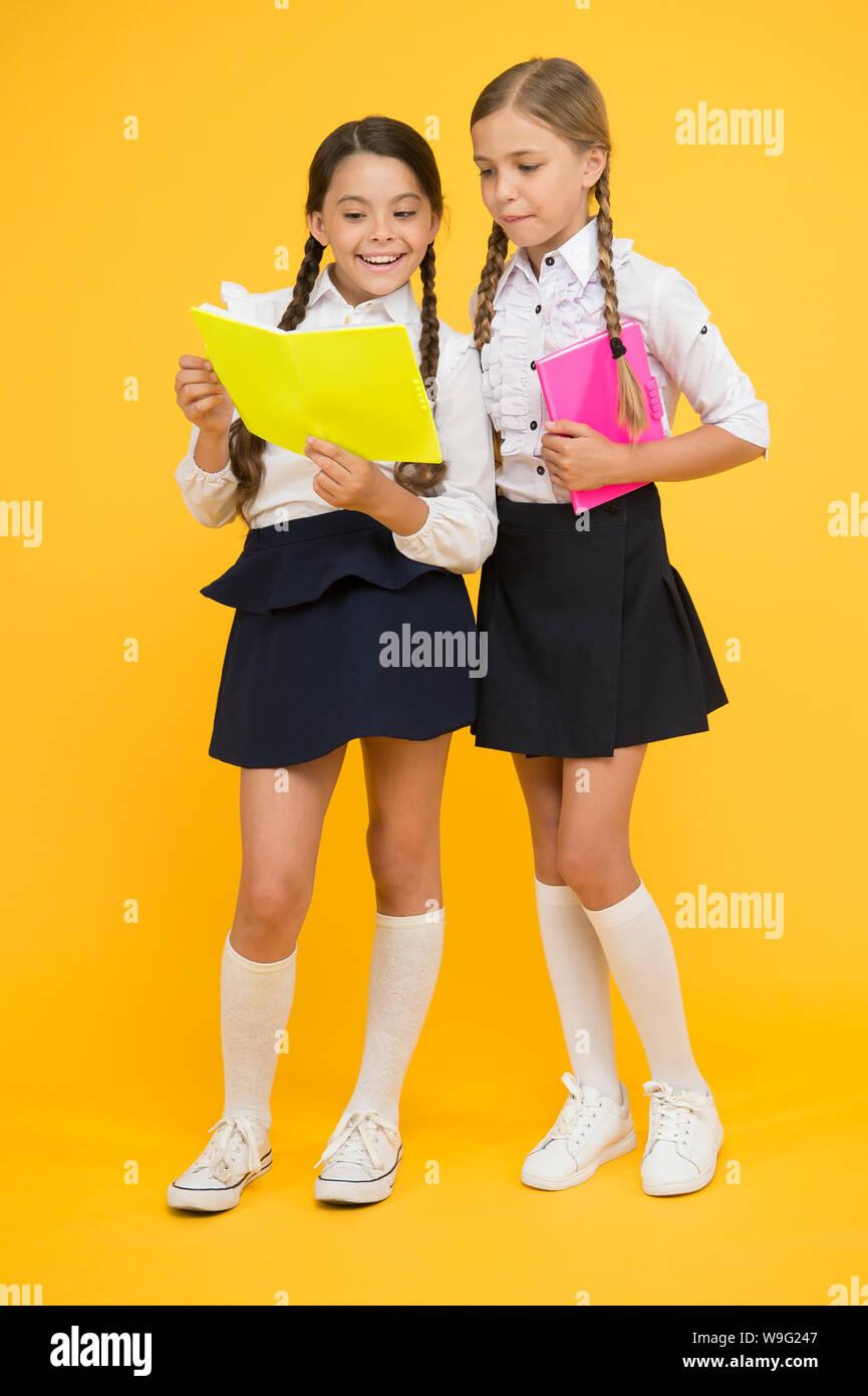 Knowledge day. School day. Kids cute students. Schoolgirls best friends excellent pupils. Schoolgirls wear school uniform. School friendship. Girl with copy books or workbooks. Study together. Stock Photo