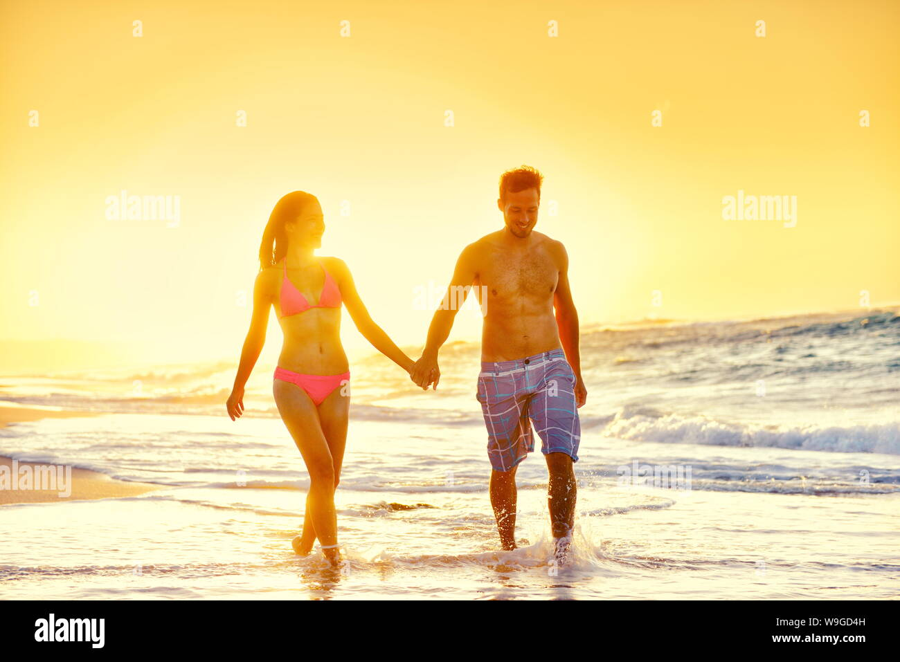 Young couple in swimwear walking at beach. Multiethnic romantic woman and man partners are holding hands while enjoying summer vacation. Loving tourists are enjoying sunset at beach. Stock Photo