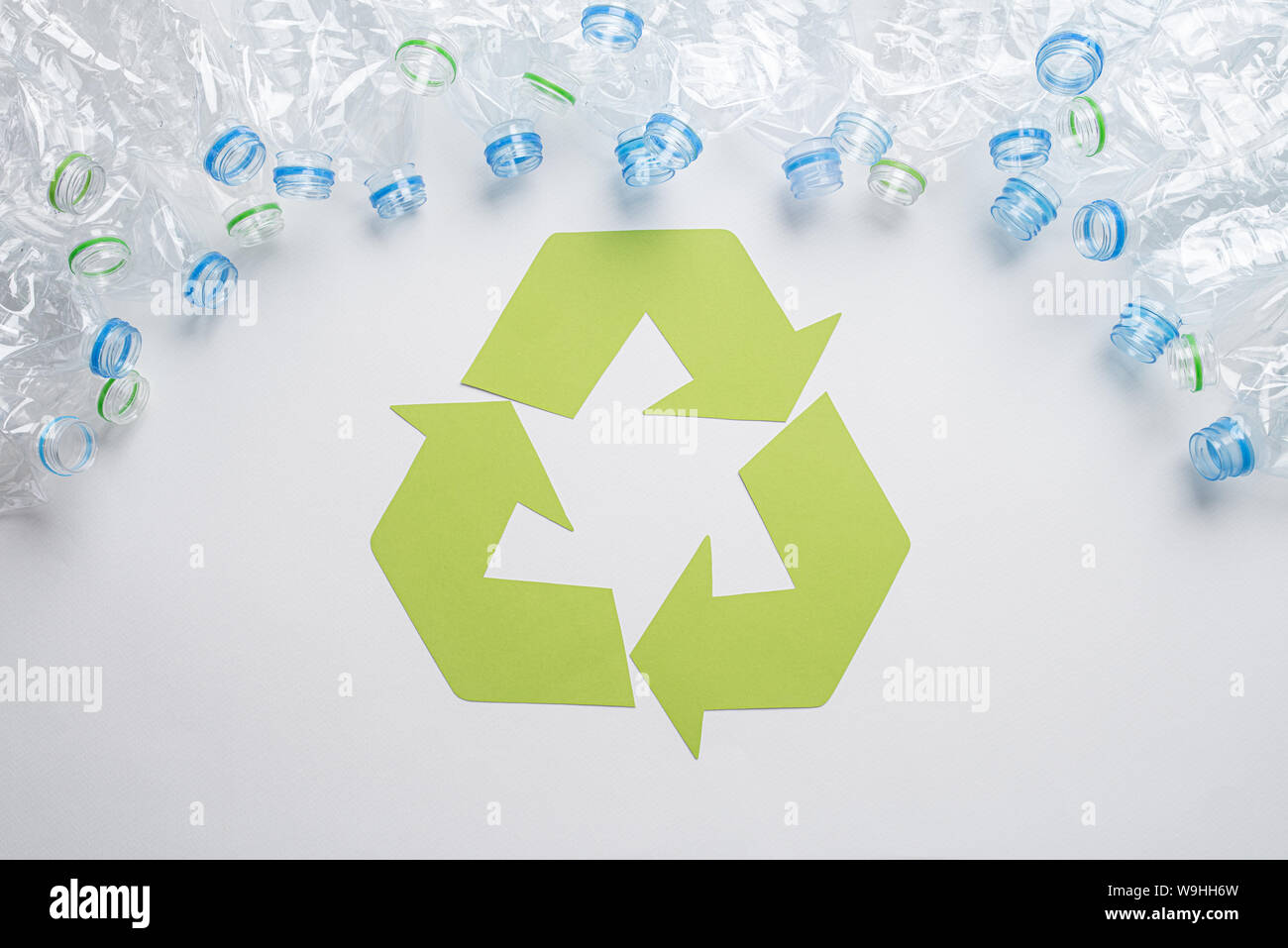 Frame of used plastic bottles with recycling symbol on wooden background. Recycle concept Stock Photo