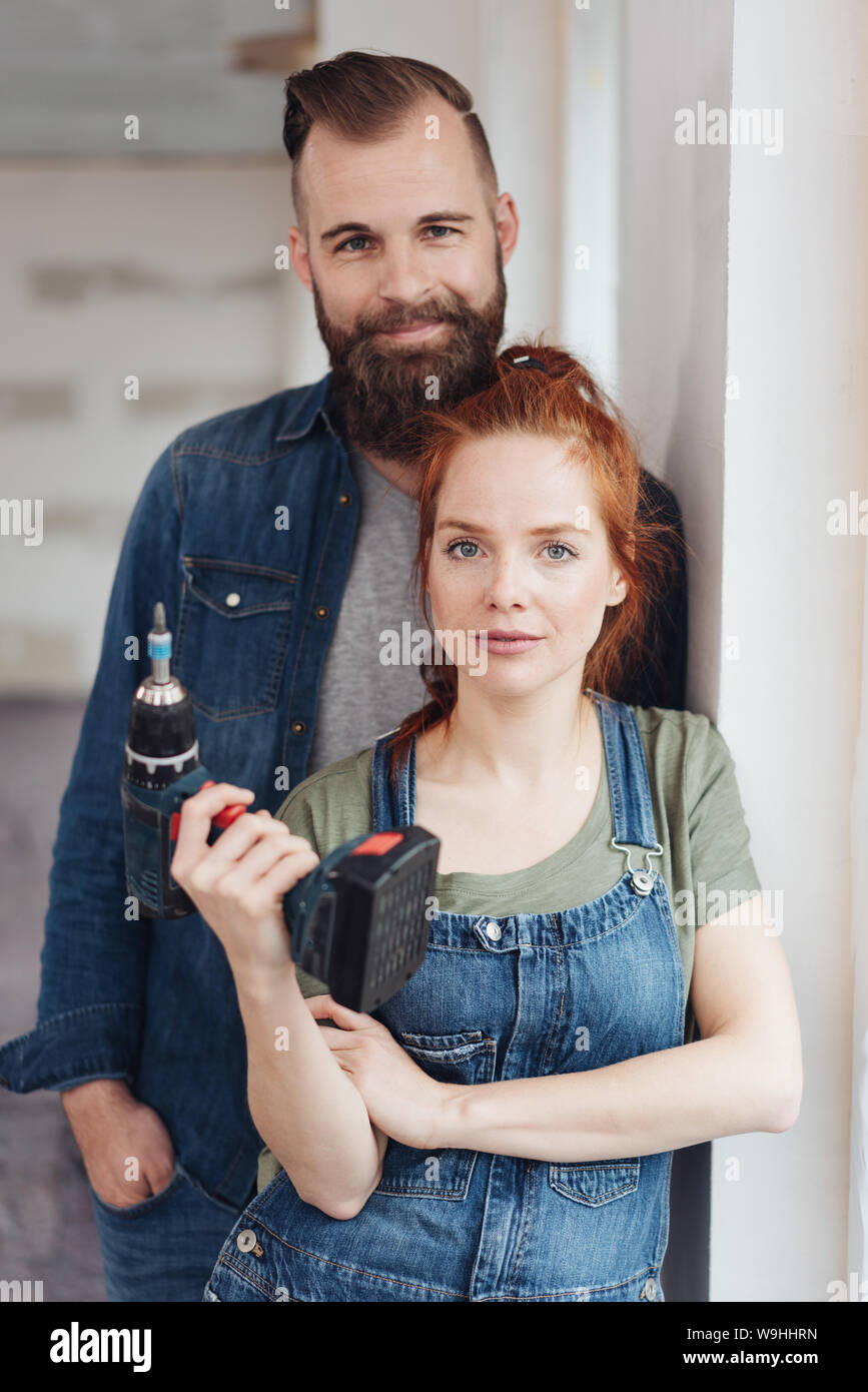 Capable young couple doing DIY renovations to their new home posing together with the woman holding an electric drill in her hand Stock Photo