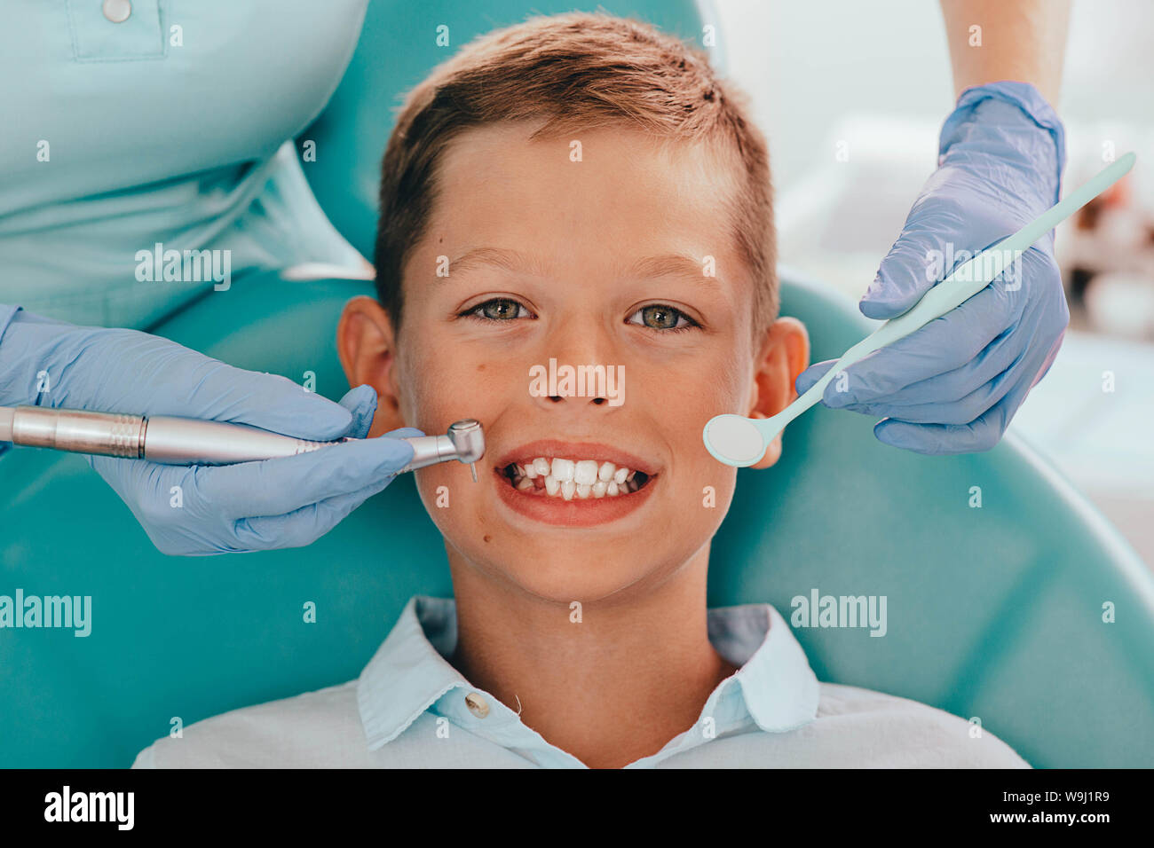 Cute boy smiling while teeth exam   Happy boy sitting in