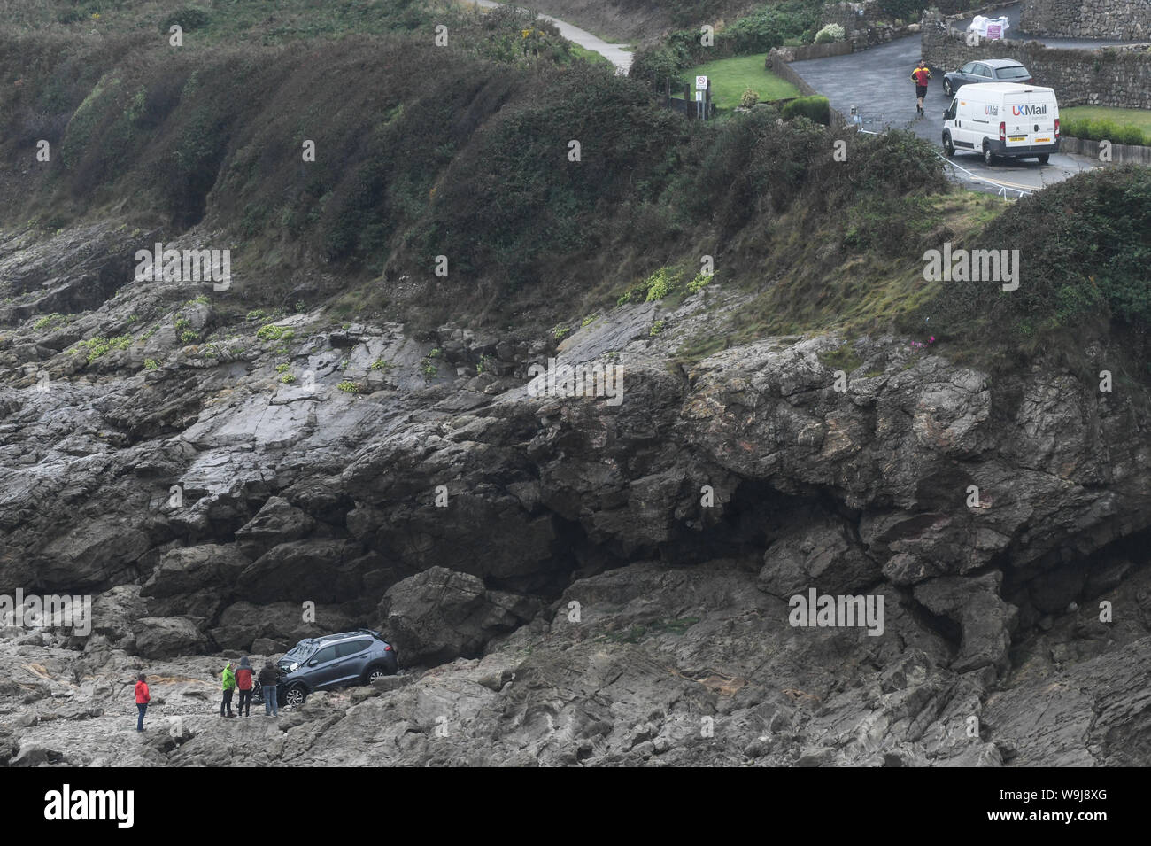 Swansea, Wales, UK. 14th August, 2019.  A damaged car remains stranded at the bottom of cliffs at Limeslade Bay, near Mumbles, Swansea, south Wales after it plunged into the sea on Tuesday morning. The driver was taken to hospital and detained under the Mental Health Act but was not seriously hurt.  Credit : Robert Melen/Alamy Live News. Stock Photo