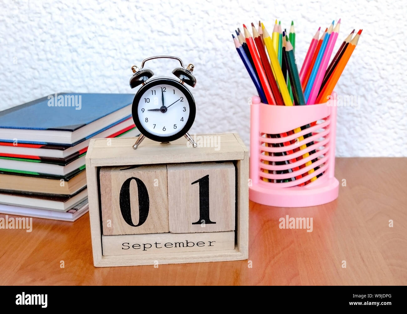 intermittent wooden calendar with the date of the first of September and an alarm clock, colored pencils on the table, a reminder of the school, close Stock Photo