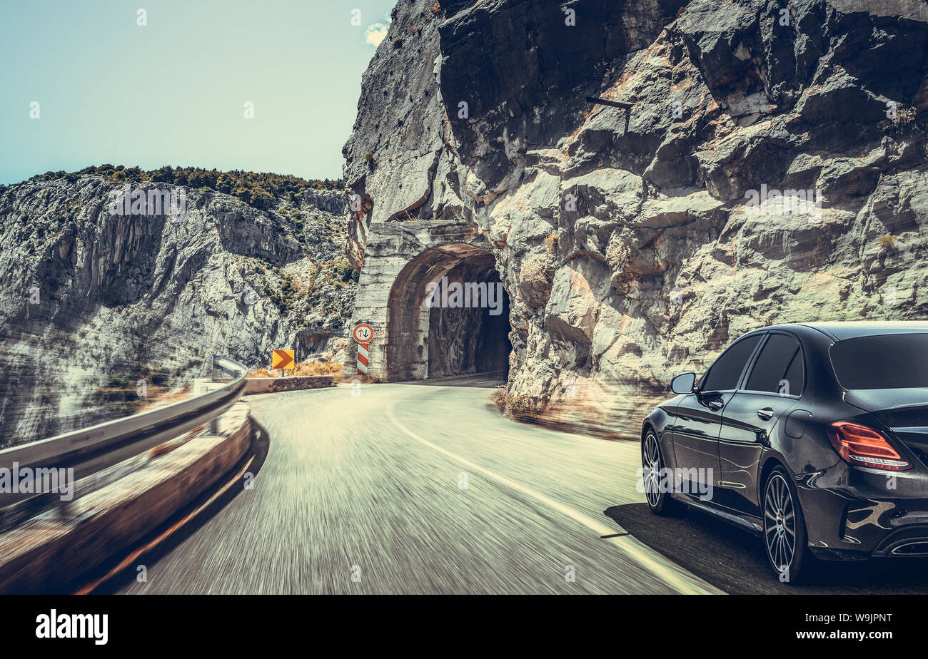 The car moves on a mountain road on a summer sunny day. Stock Photo