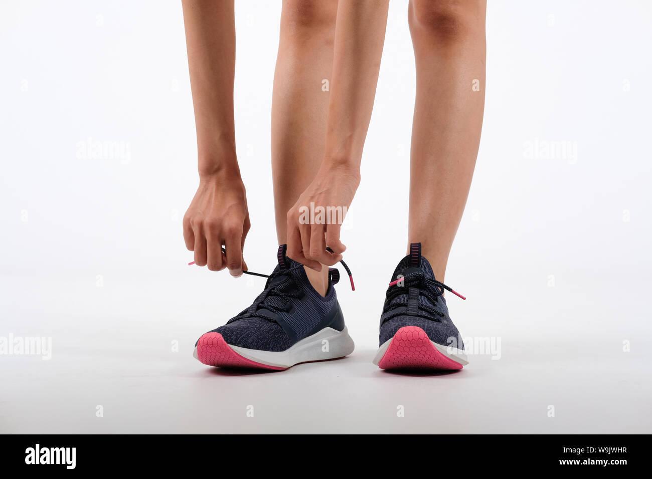 sporty fitness woman in sportswear tying sneaker shoelace on