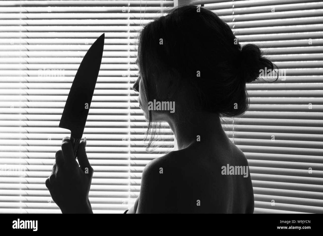 Silhouette of sad woman's head with waving hair holding a knife. concept kill Stock Photo