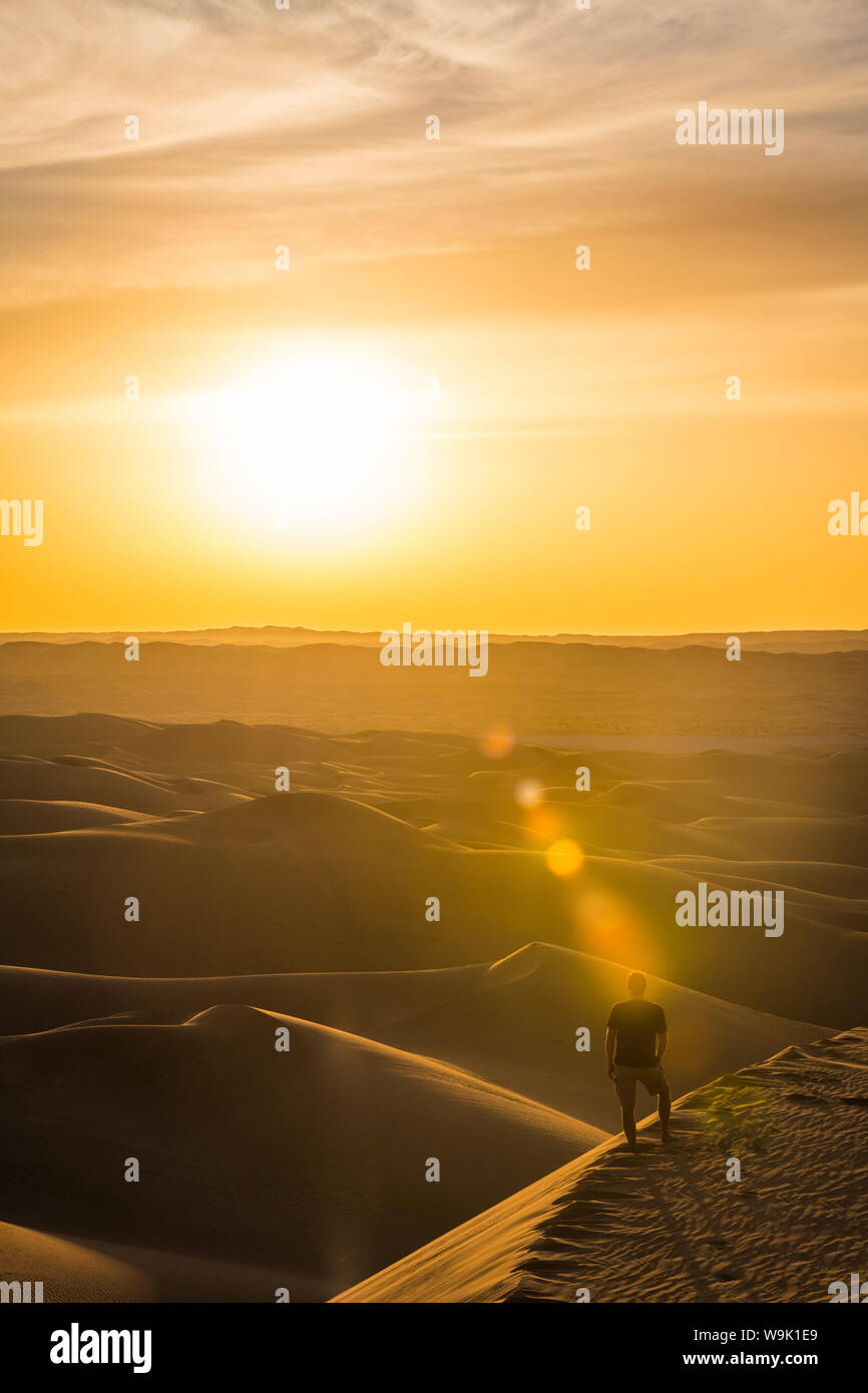 Man enjoying the sunset in the giant sand dunes of the Sahara Desert, Timimoun, western Algeria, North Africa, Africa Stock Photo