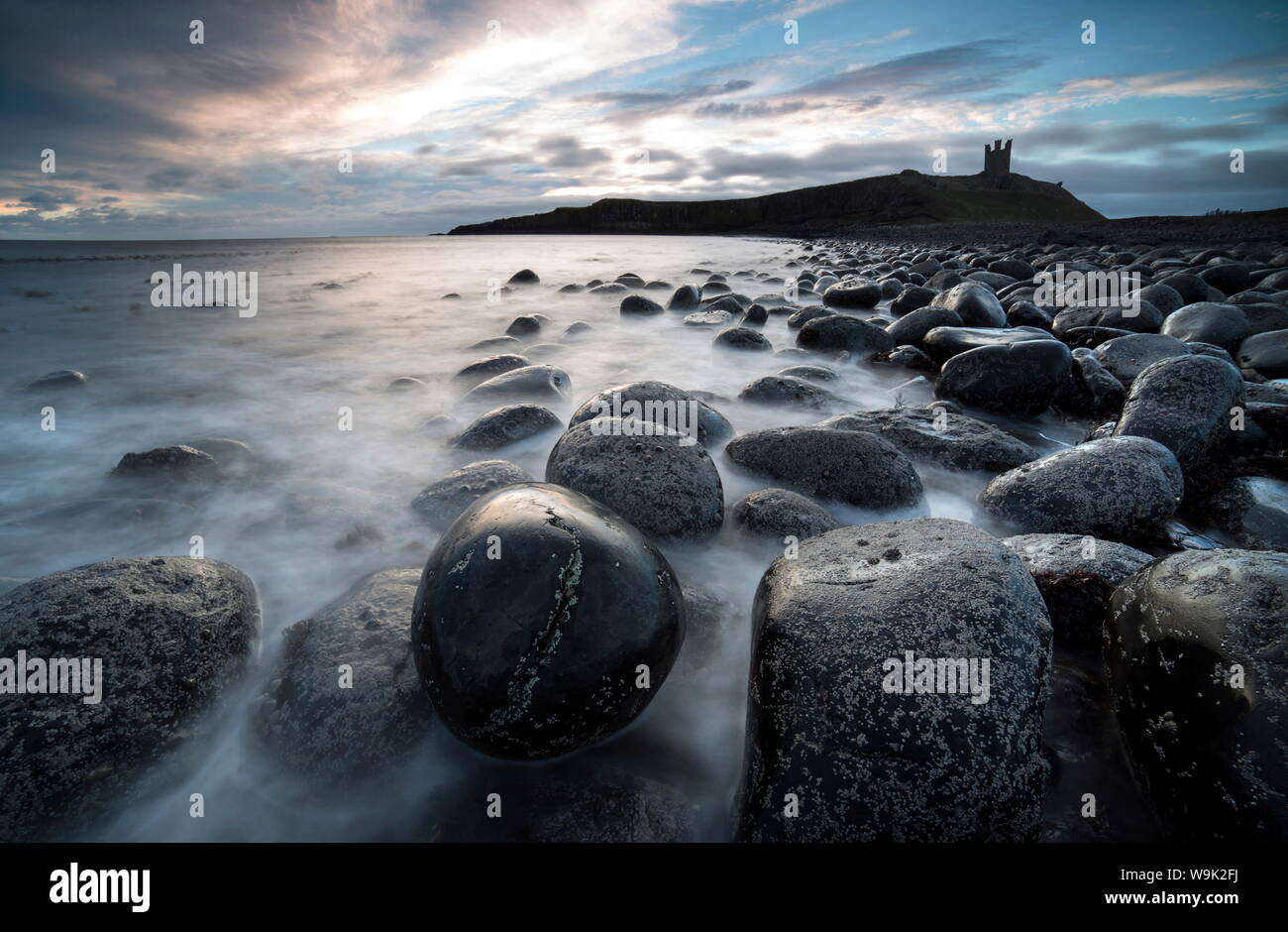 View at sunrise towards the ruin of Dunstanburgh Castle from The Rumble Churn at the Embleton Bay, Embleton, Northumberland, UK Stock Photo