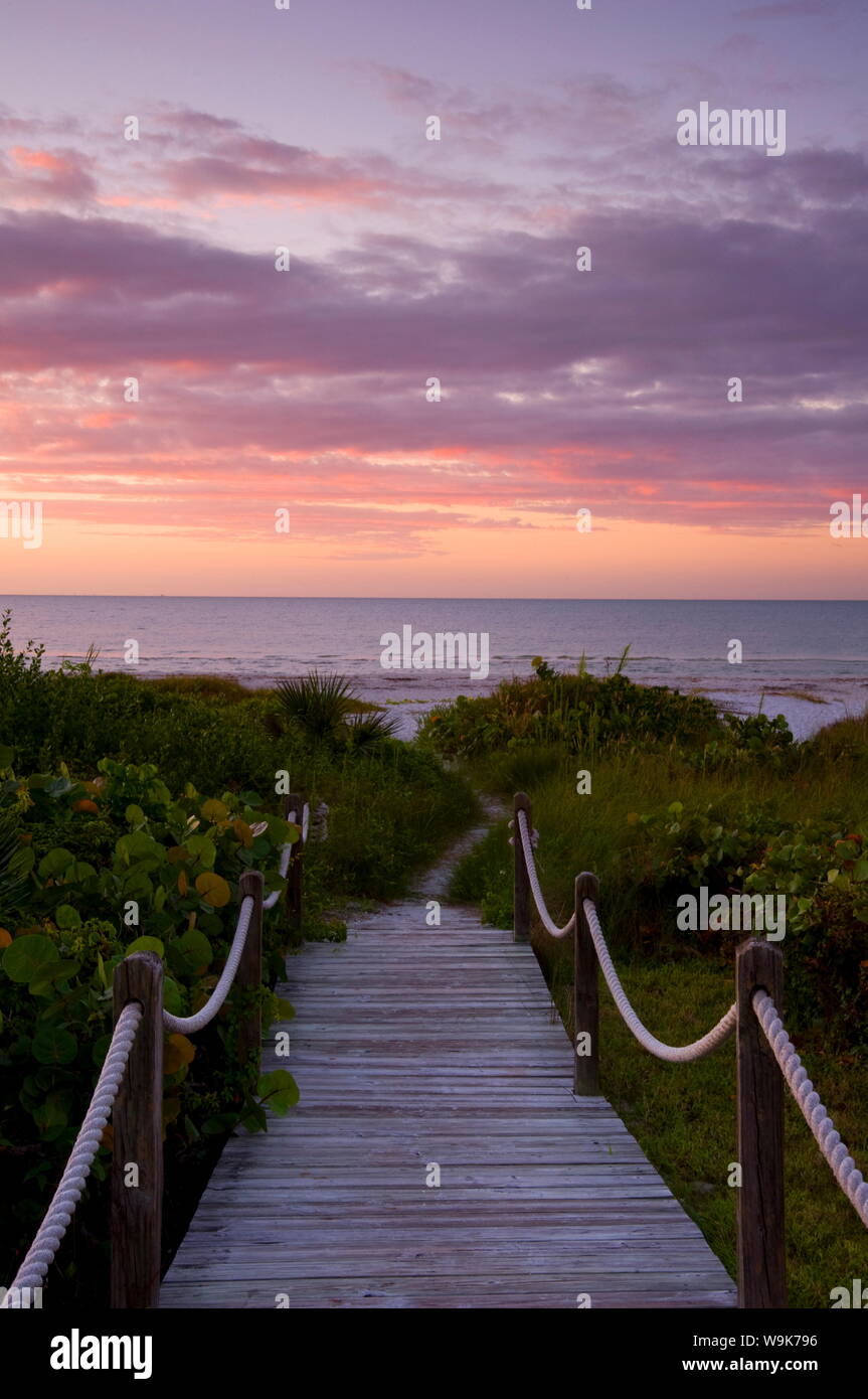 A boardwalk over sand dunes and tropical vegetation leading to the beach at sunrise, Sanibel Island, Florida, United States of America, North America Stock Photo