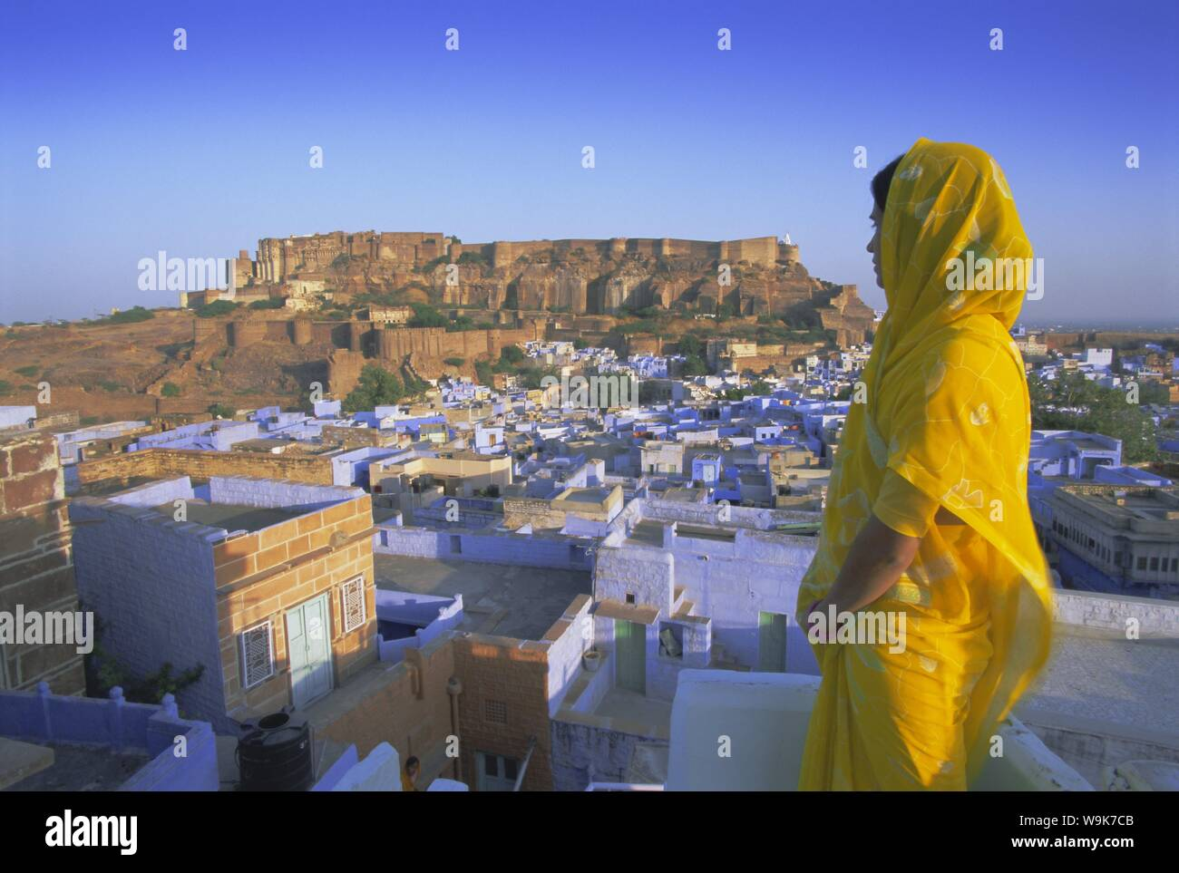 A woman in a yellow sari looking out over the 'Blue city' and fort, Jodhpur, Rajasthan State, India, Asia Stock Photo