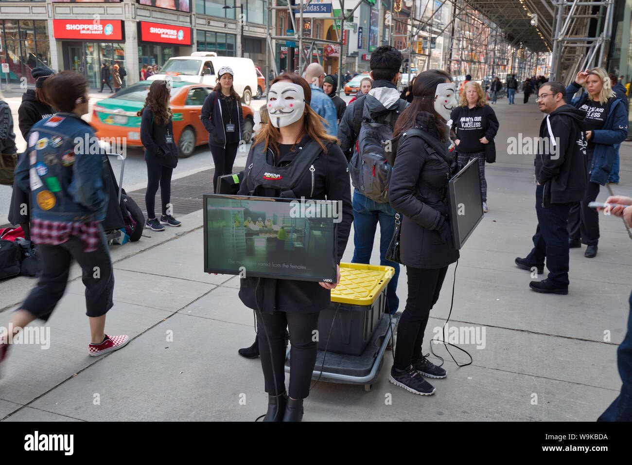 Toronto, Ontario, Canada-20 March, 2019: Protest against animal cruelty by a group of young activists wearing anonymous masks and holding TV sets that Stock Photo
