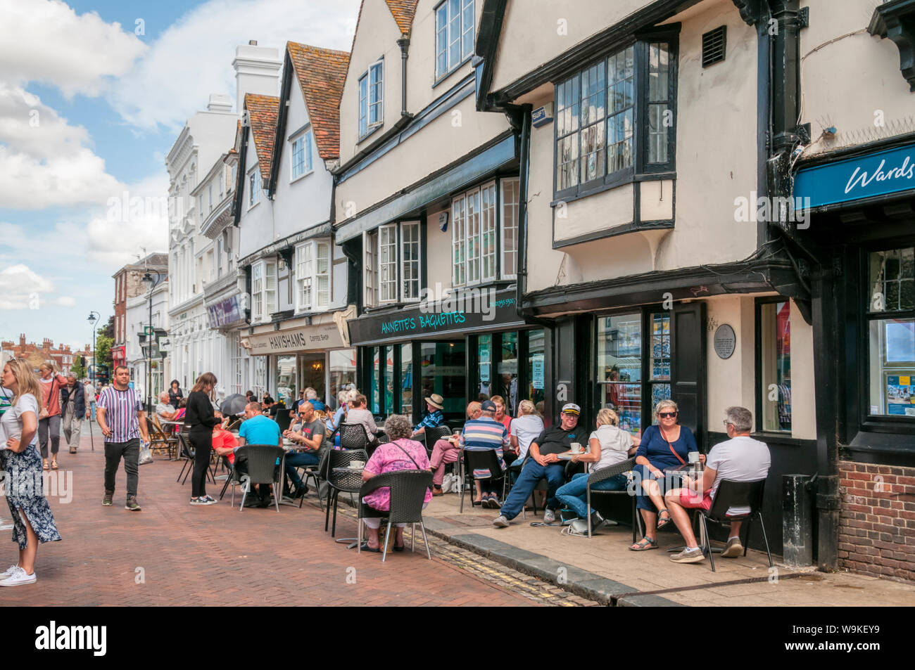 People sitting outside cafes in Court Street, Faversham, Kent. Stock Photo