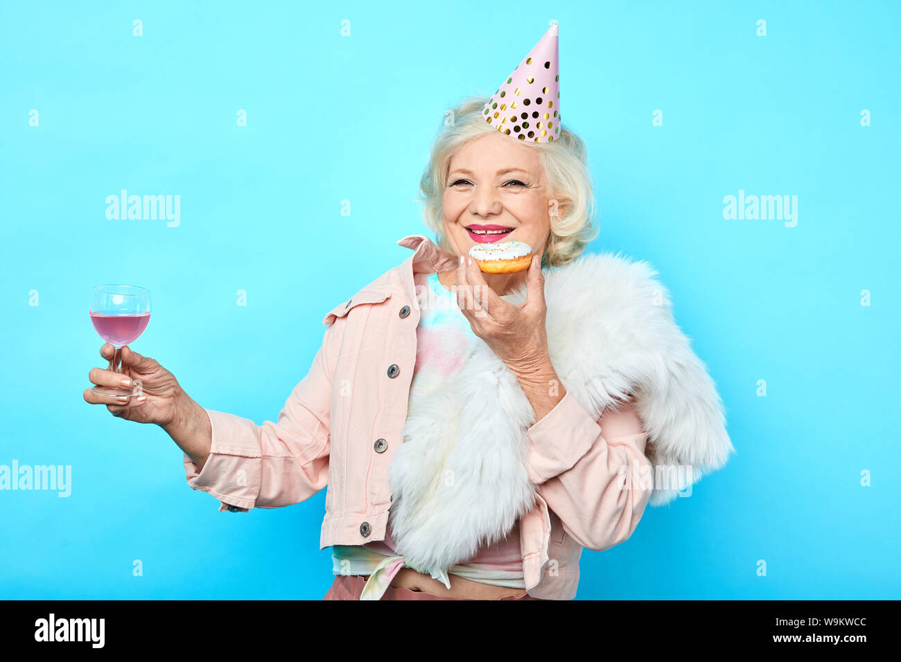 senior charming woman having fun on her Birthday. isolated blue background, happy oldness. studio shot Stock Photo