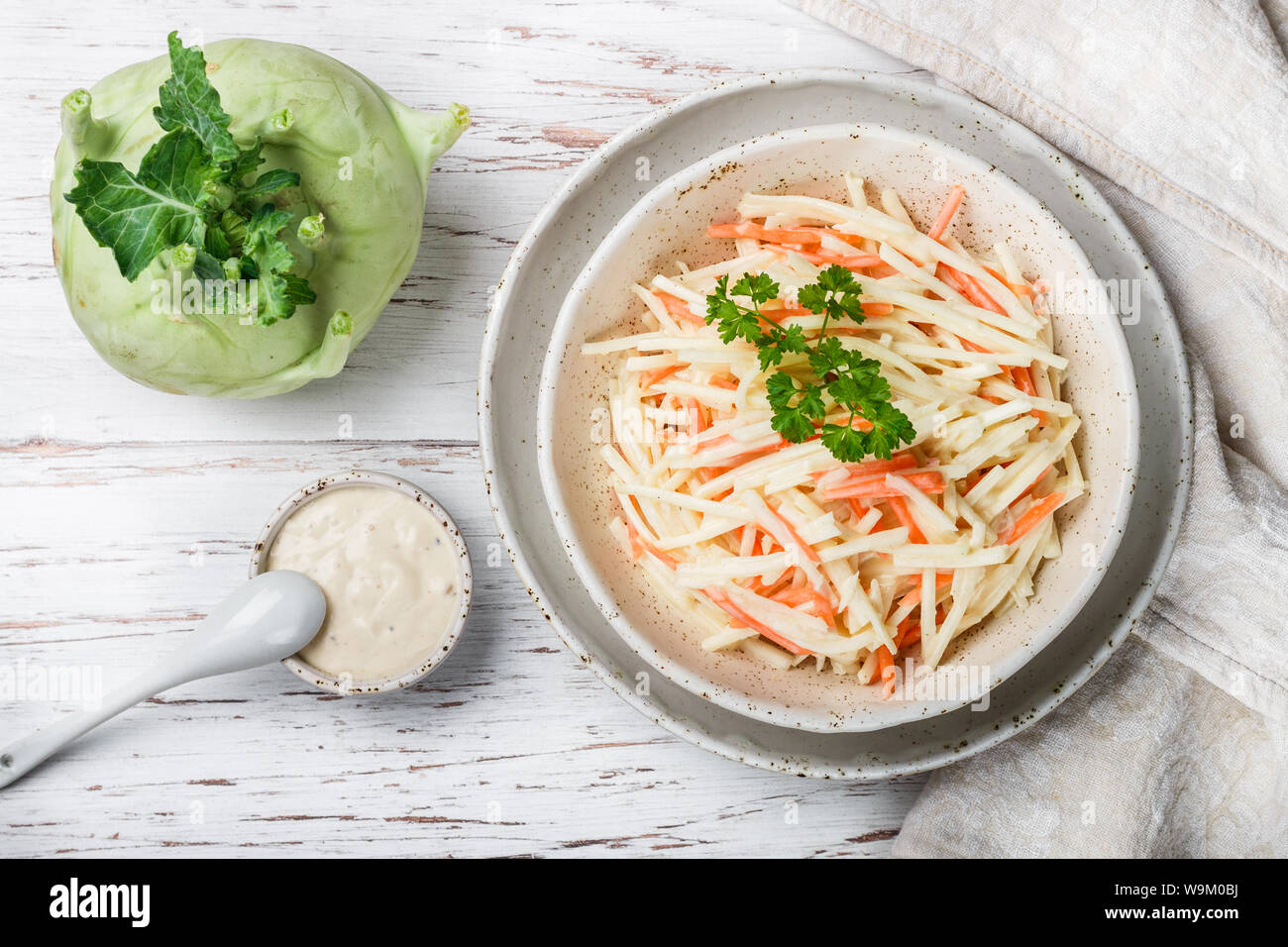 Vegetable salad of cabbage kohlrabi with carrots and Apple with dressing of natural yogurt or mayonnaise with parsley and spices. Vegetarian cuisine. Stock Photo