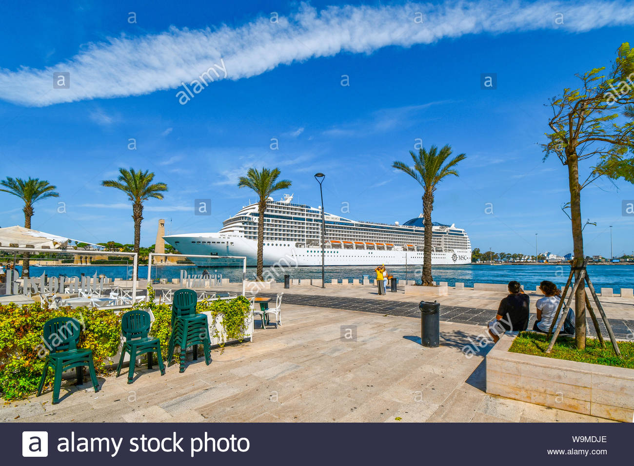Tourists watch as a massive cruise ship pulls into the narrow port on the Adriatic Sea in the mediterranean city of Brindisi, Italy - Stock Photo