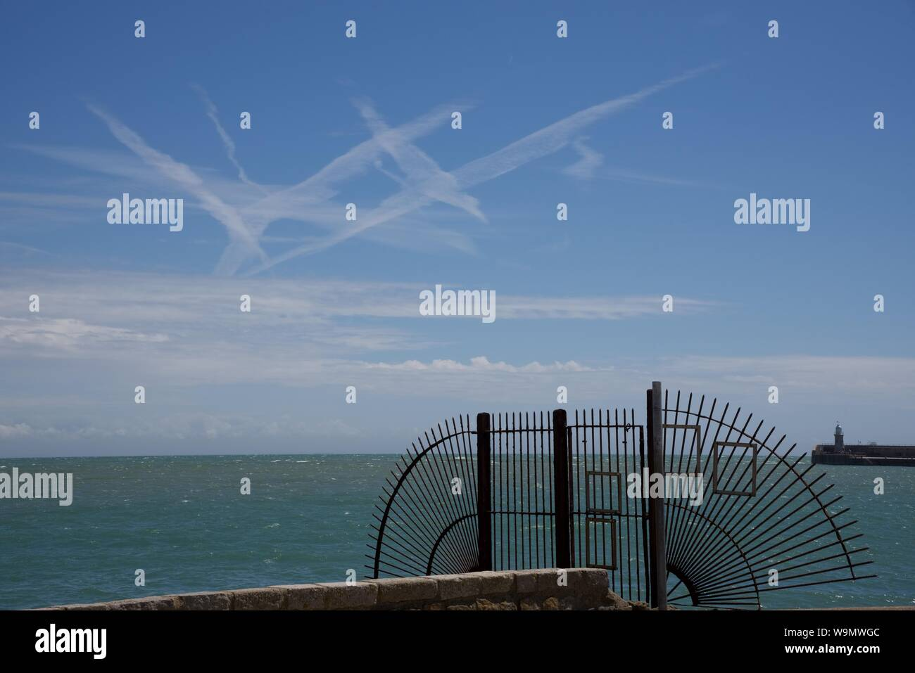 Diffused condensation trails from passenger jets over the English channel seen from Folkestone harbour Stock Photo