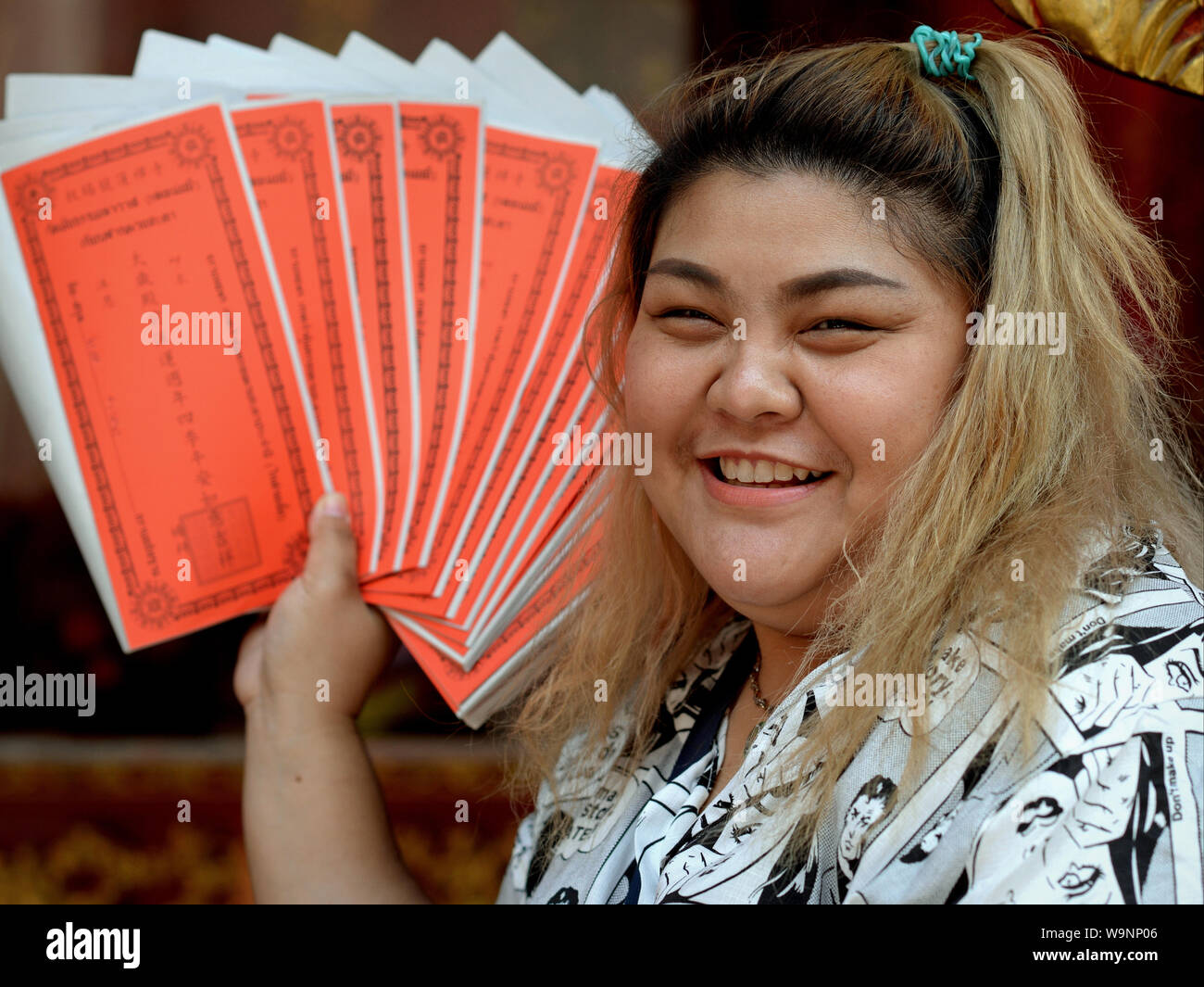 Young, full-figured Thai Chinese woman shows sheets of joss money and smiles for the camera. Stock Photo