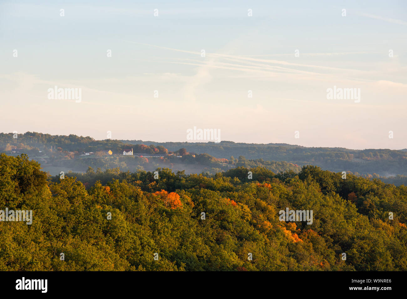 Morning mist rises over a dense forest in the Perigord region of France Stock Photo