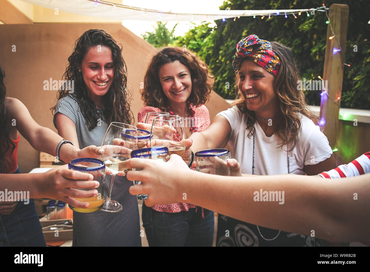 Group of happy friends cheering with glasses at dinner outdoor in terrace. Teenager and mothers having fun while drinking and eating. Focus on glasses Stock Photo