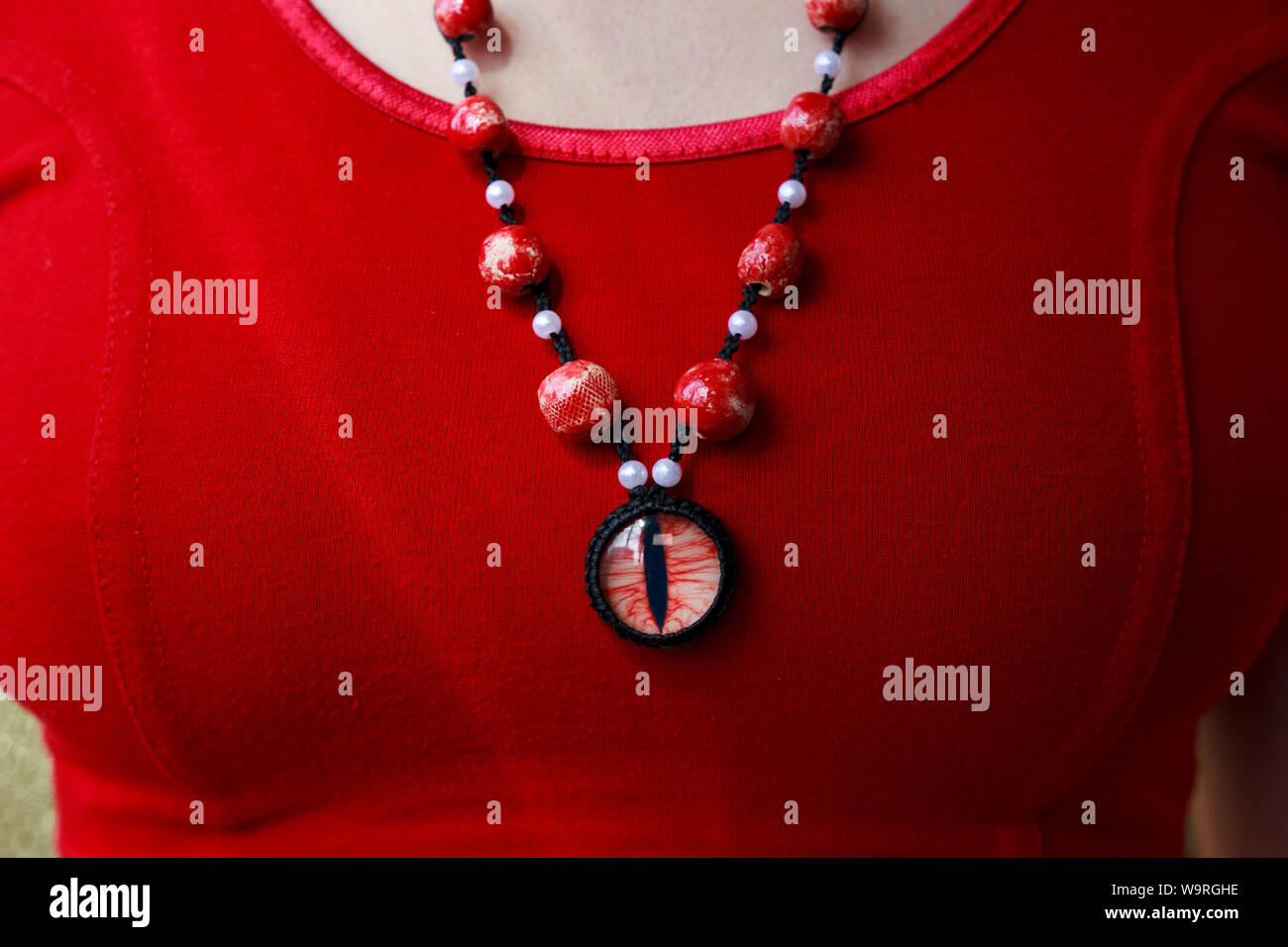 dragon red eye cabochon and ceramic beads. necklace on a young girl on a red background. Amulet Stock Photo