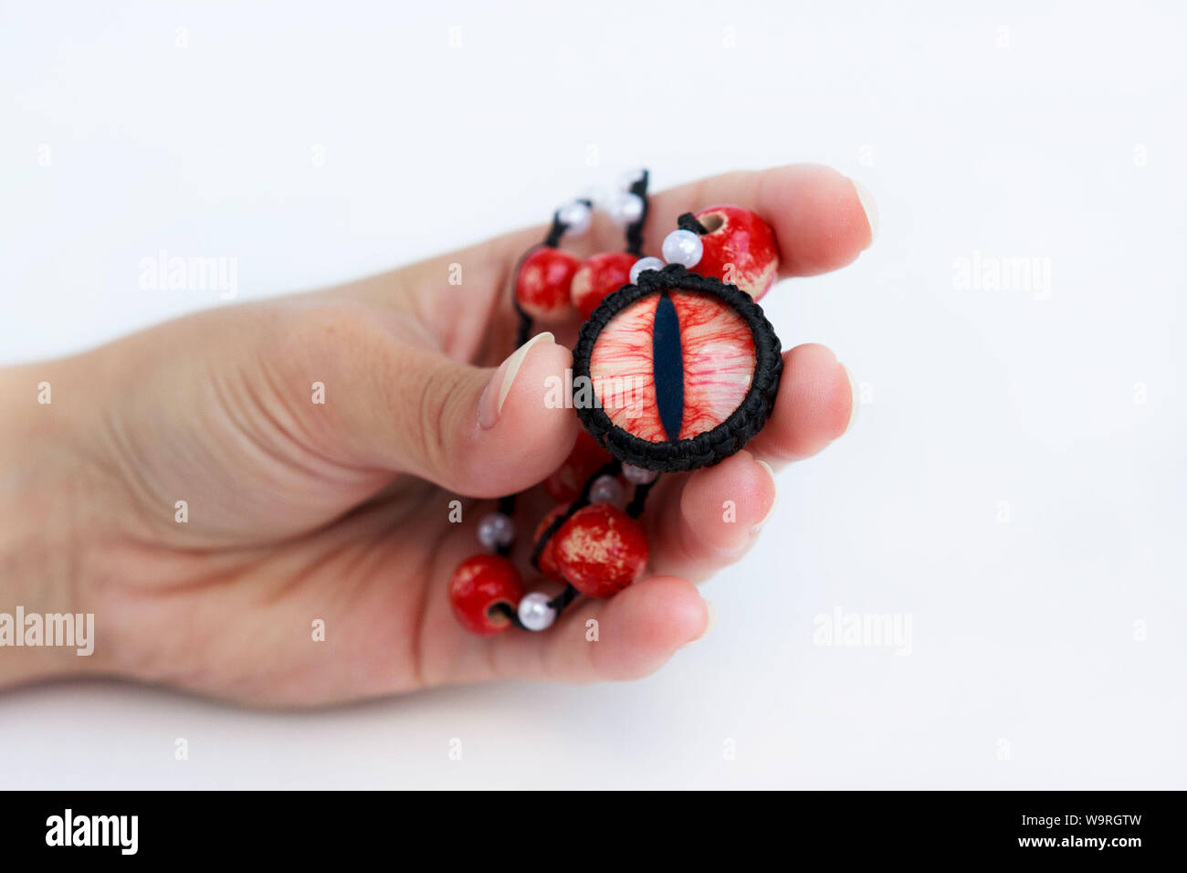 dragon red eye cabochon and ceramic beads in a girl s hand on a white background. Amulet Stock Photo