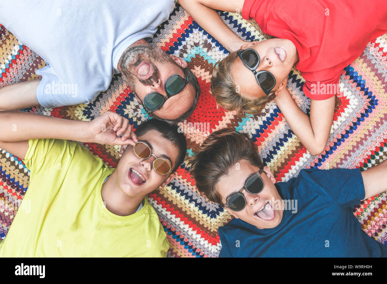 Father and sons enjoying together lying on a colorful blanket. Four men of different ages stick their tongue out with sunglasses. Group of people enjo Stock Photo