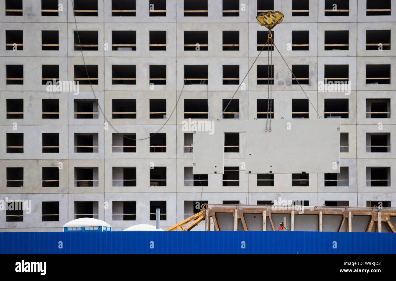 crane unload reinforced concrete walls from the car for the future high-rise building. construction site behind a blue fence. panel house. reportage Stock Photo