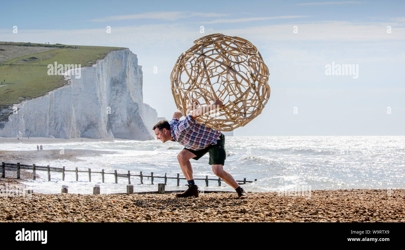 Cuckmere Haven, UK. 15 August, 2019.  Artist Keith Pettit places the first a series of steam-bent chestnut spheres on the beach at Cuckmere Haven in East Sussex. Made in collaboration with trug maker Charlie Groves, the complex shapes are inspired by the skeletal remains of ancient coccoliths - the calcium carbonate remains that make up the chalk of the South Downs. The exhibition 'What Lies Beneath' will be at the iconic coastguard cottages overlooking the Seven Sisters cliffs (pictured). Credit: Jim Holden/Alamy Live News Stock Photo