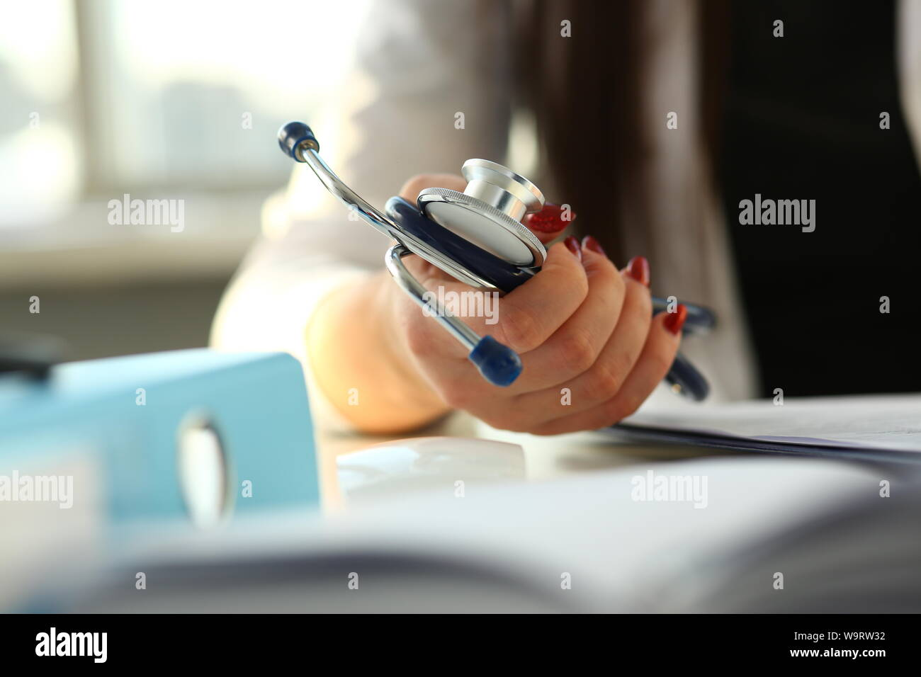 Female doctor hand hold phonendoscope in medical Stock Photo