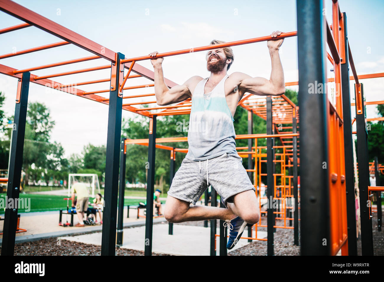 strong athlete doing pull-up on horizontal bar. Muscular man doing pull ups on horizontal bar in park. Gymnastic Bar During Workout. training strongma Stock Photo