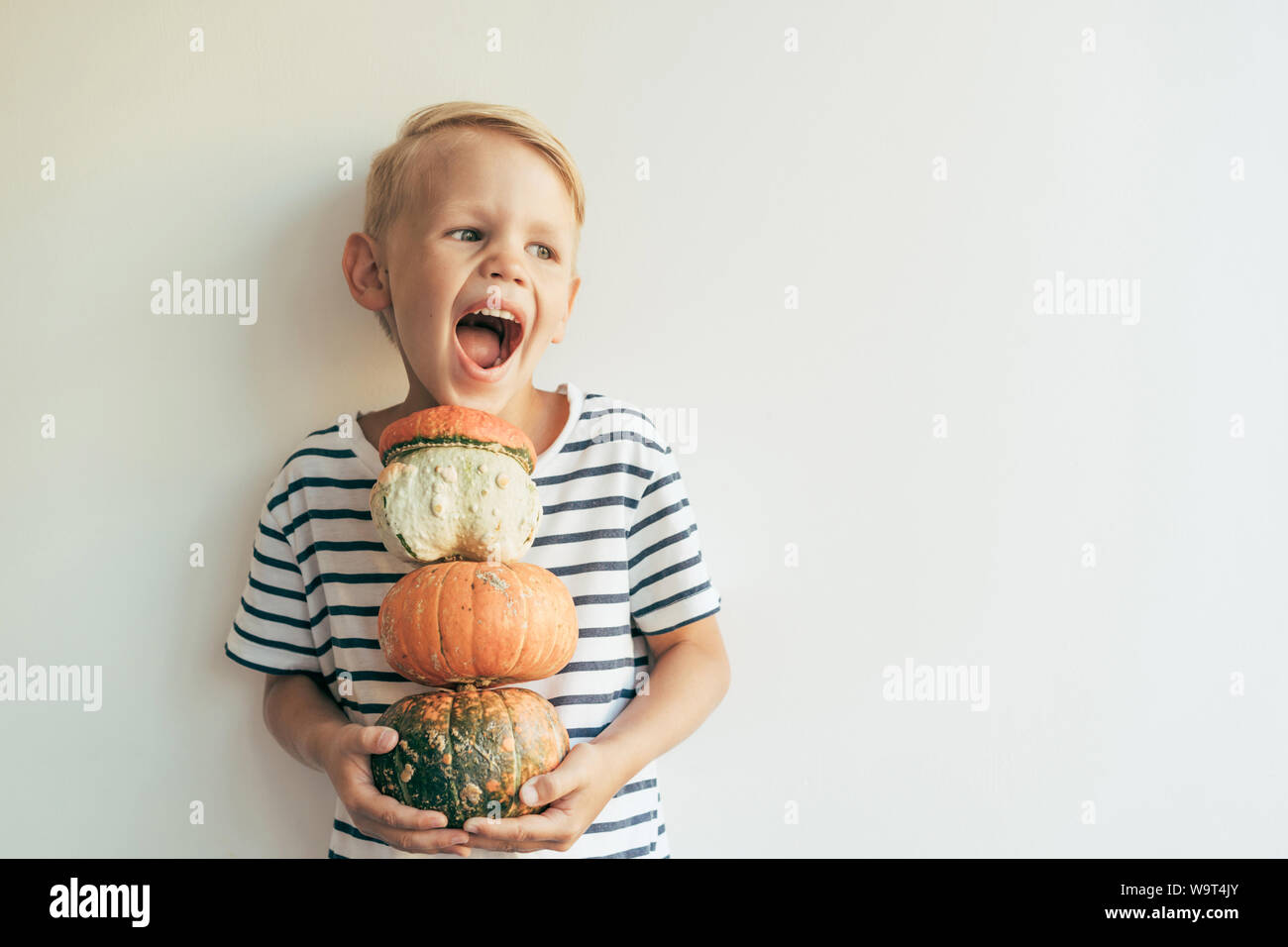 the boy laughs and holds a stack of pumpkins Stock Photo