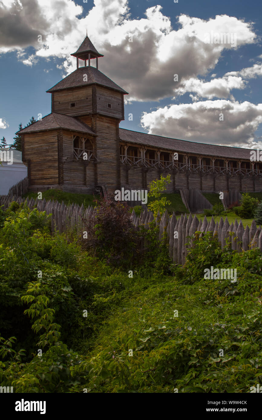 Bottom view of an old wooden fortress with a high watchtower against blue cloudy sky, selective focus Stock Photo