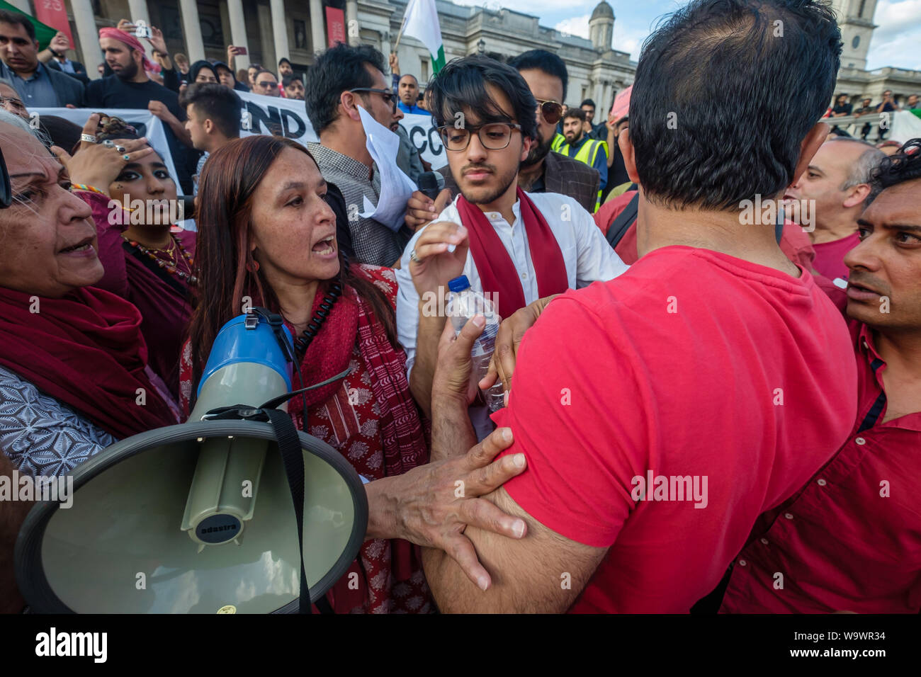 London, UK. 15th August 2019. Protesters argue at the protest in Trafalgar Square on Indian Independence Day condemning the arrests and human rights abuses in Kashmir and Modi's revocation of Article 370 of the Indian Constitution after a speaker called for only Kashmiri flags to be shown. A large group of protesters had come with Pakistani flags and after intervention by police officers the protest split into two groups. Peter Marshall/Alamy Live News Stock Photo